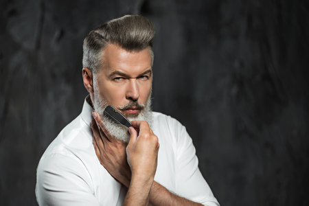 Portrait of stylish professional hairdresser with beard. Man wearing shirt, looking at camera and holding comb near his beard