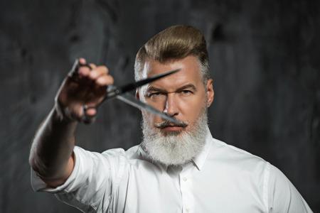 Ritratto di moda parrucchiere professionale con la barba. L'uomo indossa la camicia, guardando la fotocamera e azienda forbici vicino il suo occhio Archivio Fotografico - 54201114