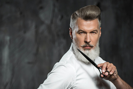 Portrait of stylish professional hairdresser with beard. Man wearing shirt, looking aside and holding scissors near his beard