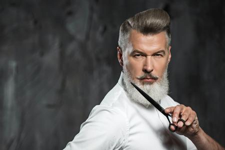 Retrato de peluquería profesional con estilo, con la barba. Hombre que usa la camisa, mira a un lado y la celebración de las tijeras cerca de la barba Foto de archivo
