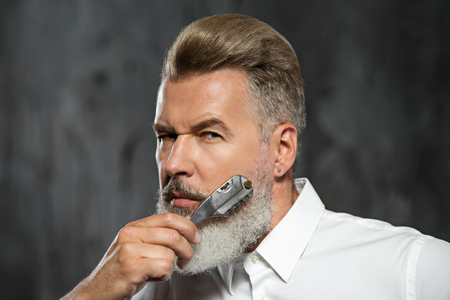 Portrait of stylish professional hairdresser with beard. Man wearing shirt, looking at camera and holding scissors near his beard Stock Photo - 54201132