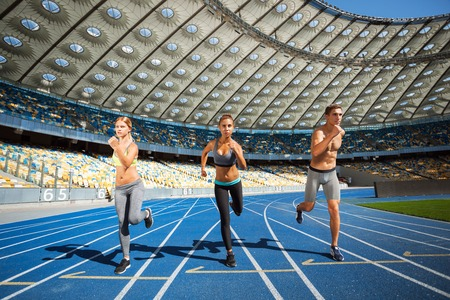 winner man: Young sporty women and man running on racetrack. Fit well formed people are at large nice modern stadium Stock Photo