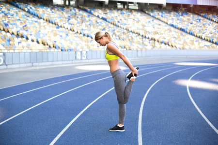 racetrack: Young beautiful blonde sportswoman stretching on racetrack outdoors. Fit woman is at large nice modern stadium