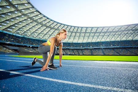 Jonge mooie blonde sportvrouw is klaar om te draaien op circuit buiten. Fit vrouw is op vrije voeten mooi modern stadion
