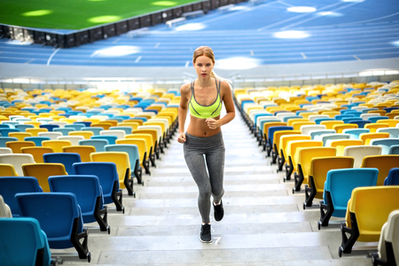 sportswoman: Young beautiful blonde sportswoman running on stairs outdoors. Sportswoman is at large nice modern stadium