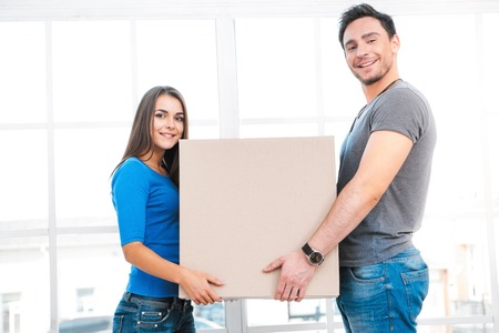 moving box: Happy young couple carrying moving box. Young family holding cardboard box while moving to new home. Woman and man smiling and looking at camera
