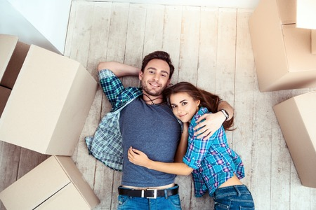 Happy young couple lying on floor near moving boxes. Young family moving to new home. Woman and man smiling and looking at camera Stockfoto