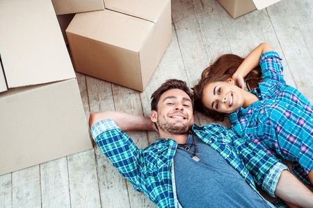 Happy young couple lying on floor near moving boxes. Young family moving to new home. Woman and man smiling and looking at camera 免版税图像