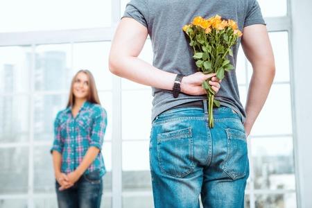 Romantische foto van gelukkige jonge paar. Jonge mens die verrassing voor zijn vriendin. Man met boeket van gele bloemen achter zijn rug
