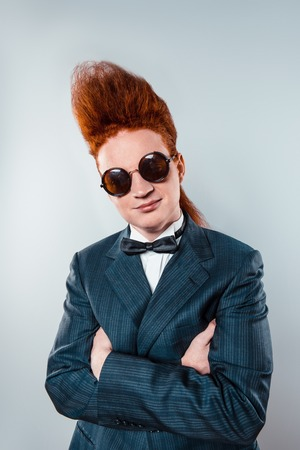 bouffant: Stylish redheaded young man with bouffant on head. Boy wearing suit with bow-tie and glasses, and looking at camera