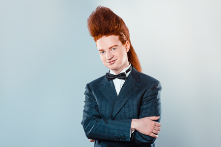 bouffant: Stylish redheaded young man with bouffant on head. Boy wearing suit with bow-tie and looking at camera Stock Photo