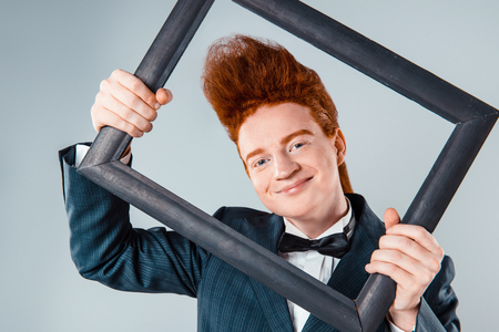 Stylish redheaded young man with bouffant on head. Boy wearing suit with bow-tie and looking at camera through frame