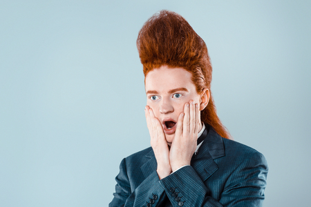 Stylish redheaded young man with bouffant on head. Shocked boy wearing suit with bow-tie Stock Photo