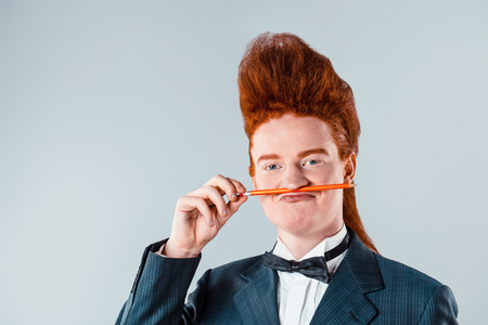 cool people: Stylish redheaded young man with bouffant on head. Boy wearing suit with bow-tie, holding pencil under nose and looking at camera Stock Photo