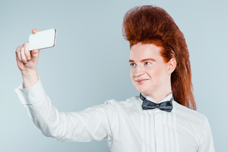 cool people: Stylish redheaded young man with bouffant on head. Boy wearing shirt with bow-tie and making selfie