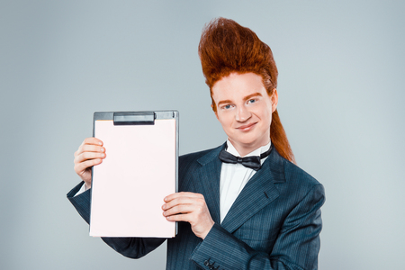 stylish men: Stylish redheaded young man with bouffant on head. Boy wearing suit with bow-tie, showing folder and looking at camera