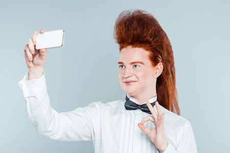 bouffant: Stylish redheaded young man with bouffant on head. Boy wearing shirt with bow-tie, showing ok sign and making selfie Stock Photo