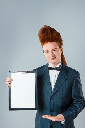 bouffant: Stylish redheaded young man with bouffant on head. Boy wearing suit with bow-tie, showing folder and looking at camera