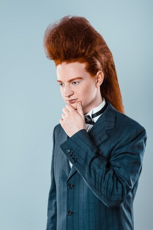 Stylish redheaded young man with bouffant on head. Thoughtful boy wearing suit with bow-tie Stock Photo