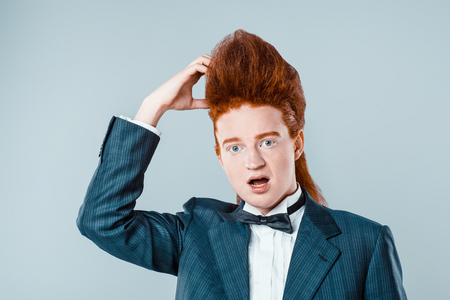 Stylish redheaded young man with bouffant on head. Thoughtful boy wearing suit with bow-tie and looking at camera
