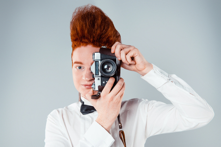 bouffant: Stylish redheaded young man with bouffant on head. Boy wearing shirt with bow-tie, holding vintage camera and looking at camera