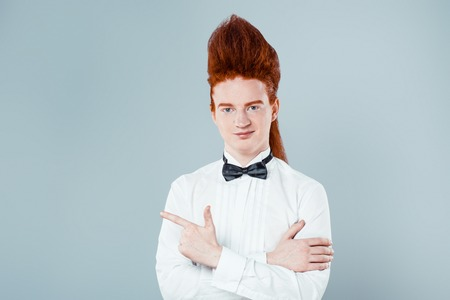 Stylish redheaded young man with bouffant on head. Boy wearing shirt with bow-tie, pointing and looking at camera Stock Photo