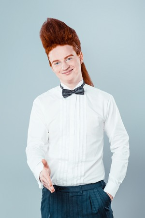cool people: Stylish redheaded young man with bouffant on head. Boy wearing shirt with bow-tie, proposing to shake hands and looking at camera Stock Photo