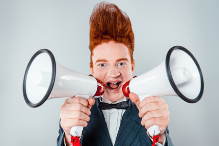 bouffant: Stylish redheaded young man with bouffant on head. Boy wearing suit with bow-tie, looking at camera and screaming with speaker