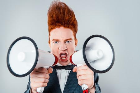 hombres guapos: joven pelirroja con estilo con el pelo cardado en la cabeza. El muchacho con traje con corbata de lazo, mirando a la c�mara y gritando con el altavoz