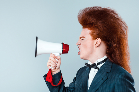 Stylish redheaded young man with bouffant on head. Boy wearing suit with bow-tie and screaming with speaker