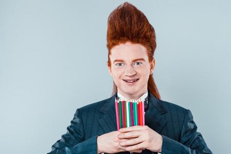 cabello rojo: joven pelirroja con estilo con el pelo cardado en la cabeza. El muchacho con traje con corbata de lazo, la celebraci�n de pegatinas de colores y mirando a la c�mara Foto de archivo
