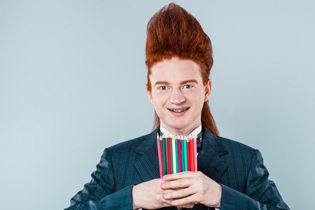 hair studio: Stylish redheaded young man with bouffant on head. Boy wearing suit with bow-tie, holding colorful stickers and looking at camera Stock Photo