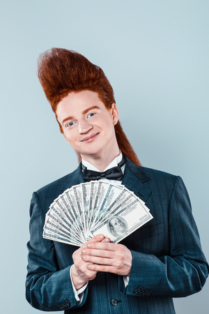 beau mec: Stylish redheaded young man with bouffant on head. Boy wearing suit with bow-tie, holding money and looking at camera Banque d'images