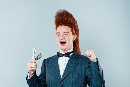 cool people: Stylish redheaded young man with bouffant on head. Happy boy wearing suit with bow-tie and holding money Stock Photo
