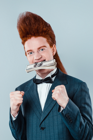 bouffant: Stylish redheaded young man with bouffant on head. Boy wearing suit with bow-tie, holding money in mouth and looking at camera Stock Photo