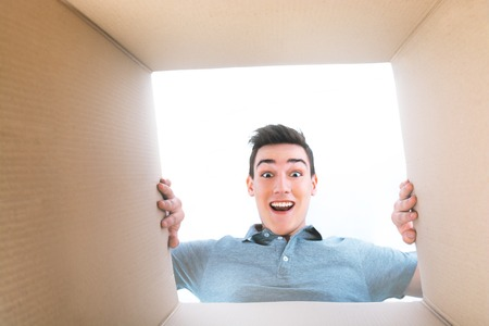 unpacking: Man smiling, unpacking and opening carton box, and looking inside