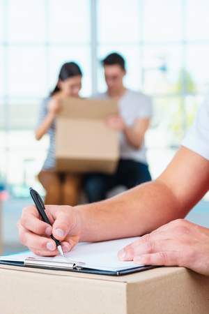 girl portrait: Delivery service worker in uniform delivering parcels to happy couple. Man with box signing document Stock Photo