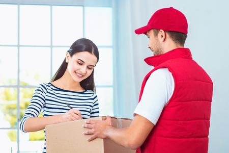 Lieferservice-Arbeiter in Uniform Paket Frau zu liefern. Frau Unterzeichnung Dokument auf Feld Lizenzfreie Bilder - 54205042