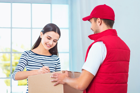 �uniform: trabajador del servicio de la salida en uniforme entrega de paquetes a la mujer. Mujer que firma el documento en el cuadro Foto de archivo