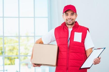 Bezorgservice werknemer in uniform te leveren pakket. Man met doos Holding document te ondertekenen en te kijken naar de camera