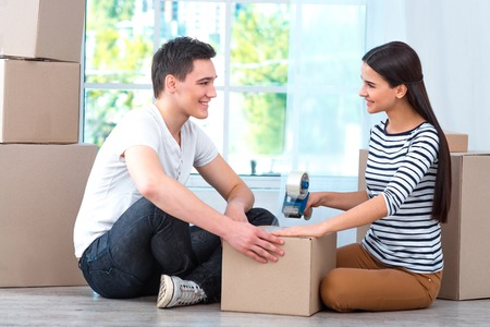portrait of woman: Happy couple smiling, packing and closing carton box, and looking at each other