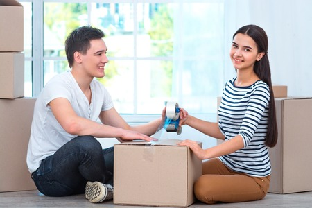 portrait of a women: Happy couple smiling, packing and closing carton box, and looking at camera