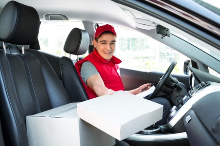 Livraison travailleur des services en uniforme la livraison des colis et assis à la voiture. Man boîte contenant, souriant et regardant la caméra Banque d'images