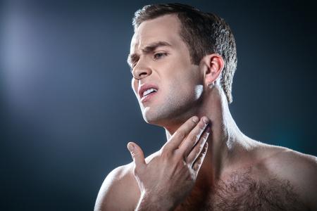 Studio portrait of handsome young man. Man with torso having skin irritation after shaving Foto de archivo