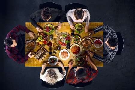 Top view creative photo of friends sitting at wooden vintage table. Friends of six having dinner. They with plates full of delicious meal and glasses with drinks Stockfoto