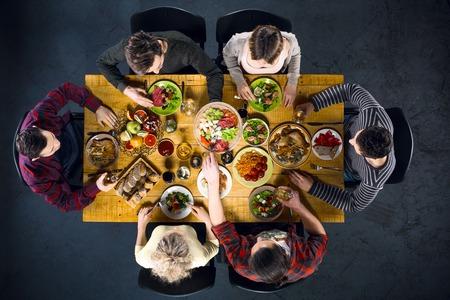 Top view photo créative d'amis assis à table en bois vintage. Amis de six dîner. Ils avec des plaques pleines de délicieux repas et des verres avec des boissons