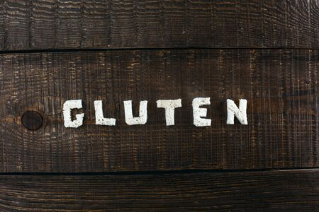 allergic ingredients: Top view studio shot of gluten-free word on wooden table