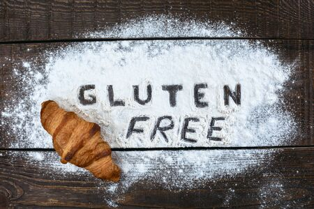 allergic ingredients: Top view studio shot of gluten-free word with flour and croissant on wooden table