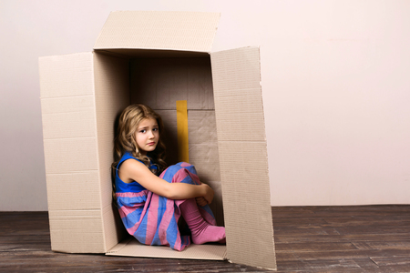 Sad childhood. Little girl sitting inside cardboard box. Girl is upset and unhappy