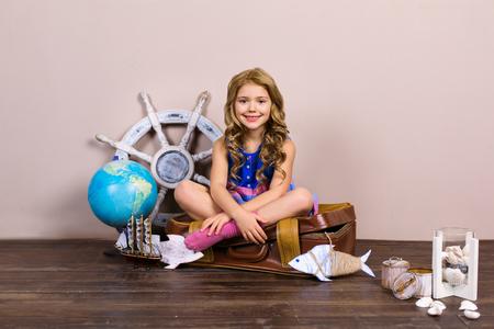 Verspielte Kindheit. Kleines Mädchen auf Reisen. Mädchen, das am Koffer nahe Globus sitzt